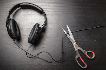 pirated: Scissors cut the wire from the headphones, and thus stop the very loud illegal pirated music on a dark background