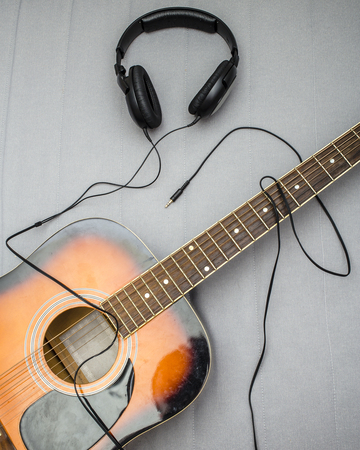 instrument cable: guitar lying on the sofa and lie next to the headphones, the wire from which form the silhouette of a guitarist playing