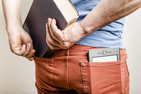 shove: in the back pocket of jeans is an e-book, a man tries to shove in a second pocket thick old paper book Stock Photo