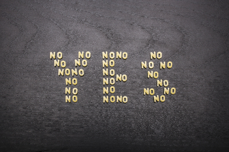 innuendo: The answer yes made up of a set of words no, with small pasta letters on a dark background of a wooden board, showing the hidden meaning and ambiguity of the agreement.