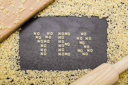 innuendo: The answer yes made up of a set of words no, with small pasta letters on a dark background wooden board surrounded by other letters of the alphabet, demonstrating the hidden meaning Stock Photo