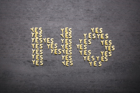 innuendo: The answer no made up of a set of words yes, with small pasta letters on a dark background of a wooden board, showing the hidden meaning and ambiguity of the agreement.