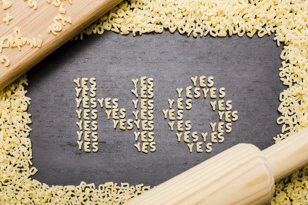 innuendo: The answer no made up of a set of words yes, with small pasta letters on a dark background wooden board surrounded by other letters of the alphabet, demonstrating the hidden meaning