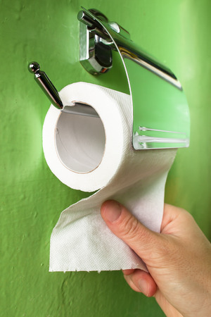 hand pulls the toilet paper in chrome holder on background green wall