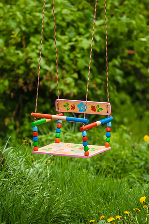 empty swing for children in the midst of green grass and trees in the rain