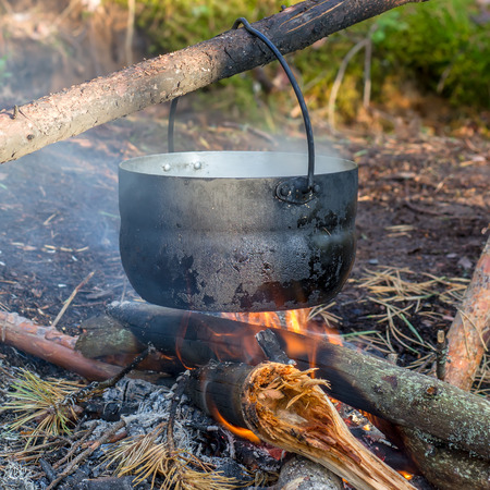 pot hanging over the fire in the forest in a hike, the water vapor from the boiler Stock Photo