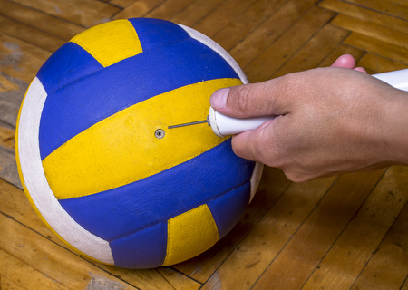 balon de voley: man is pumped volleyball on the floor Foto de archivo