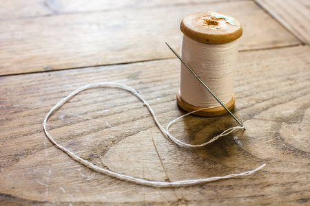 Backlighting coil with white threads and a needle stuck standing on an old wooden table Reklamní fotografie
