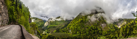 old serpentine road goes in the picturesque mountains, which are bundled cap clouds Stock Photo