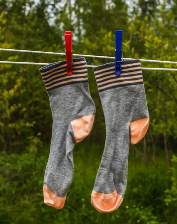 socks hanging on the rope for drying clothes on clothespins Stock Photo