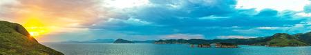 long panorama de la soirée coucher de soleil coloré dans la côte de l'océan de la zone de villégiature russe de la mer du Japon avec collines et verdure, nuages ??sur fond