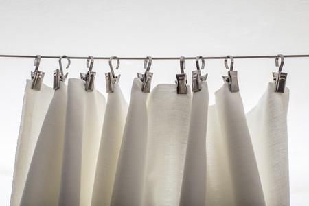 Crème-kleurige gordijn hangen op een koord op een metalen haak in wit plafond Stockfoto