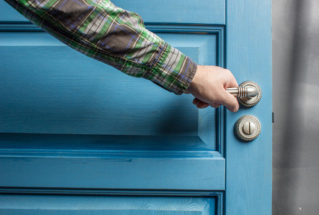 man holding on to by its metal handle in the open wooden door blue Stock Photo