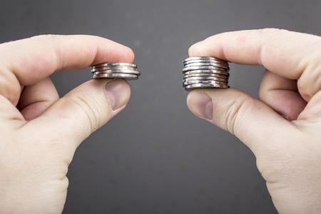 Las manos comparan dos pilas de monedas de diferentes tamaños, lo que indica el retorno de la inversión.