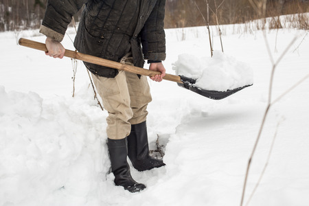 shoveling: man removes shoveling snow from the track, using a spade in the winter in the village Stock Photo