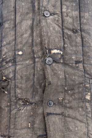 holey: man dressed in shabby old worn working clothes with patches