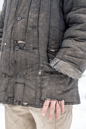 patched: man dressed in shabby old worn working clothes with patches, and put his hand in his pocket full of holes