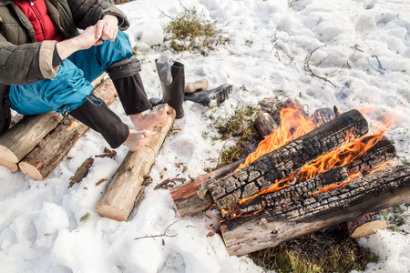 warms: A man warms his hands and feet near the fire in the pine forest covered with snow in winter