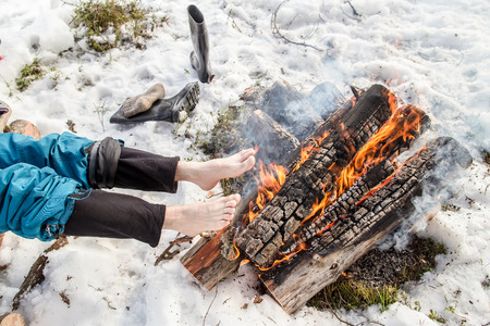 warms: A man warms his barefoot feet near the fire in the pine forest covered with snow in winter