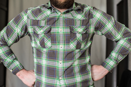 stout, bearded man in a checked shirt standing arms akimbo resolutely