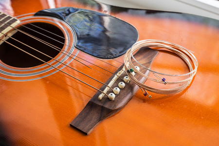 New guitar strings put on the acoustic guitar ready for replacement Stock Photo