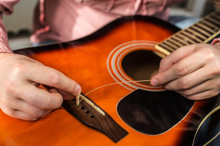 man changes hands old ripped guitar strings on the acoustic guitar on the new