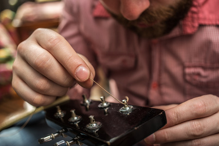 a man in a plaid shirt inserts new guitar strings to the acoustic guitar Imagens - 70480492