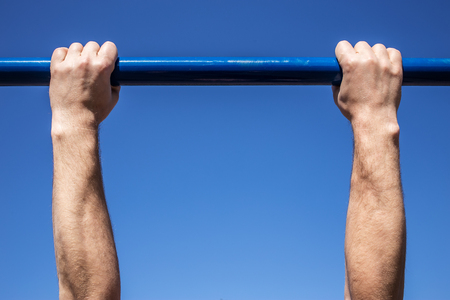 Powerful hands of man which is is tightened on a horizontal bar a blue sky background Standard-Bild