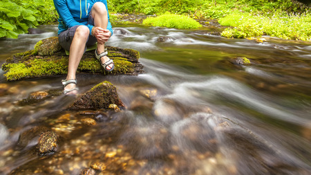 against the flow: person sits on the stone covered with moss in the center of rapid flow of the river, holding his feet in clear water against the background of juicy greenery Stock Photo