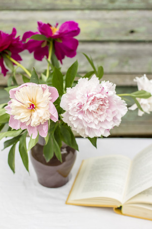 Vase of beautiful peony and the open book on a table covered with a tablecloth, outdoor, against a background the old wooden wall with peeling paint  lovely summer afternoon
