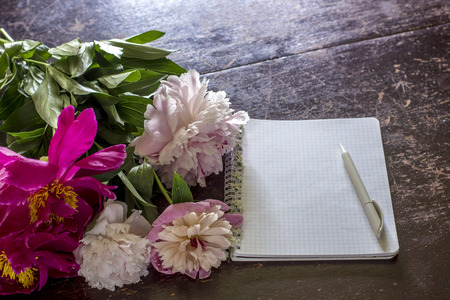 pluma de escribir antigua: Peonies a beautiful bouquet lies on the old table with peeling paint, lies next a notepad and pen