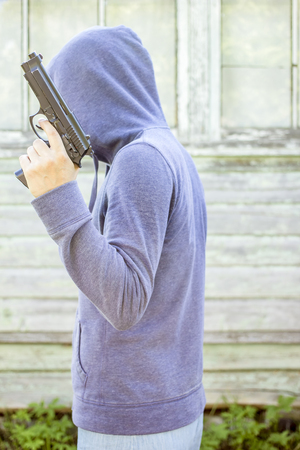 Man in hoodie holding in his hand pistol on a background the old wooden walls outdoors Stock Photo