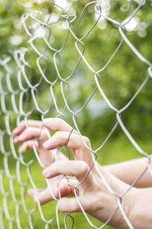 Hands holding fence outdoors in the daytime, in a village