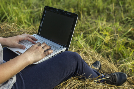 Girl working on a laptop on a haystack a summer evening 스톡 콘텐츠