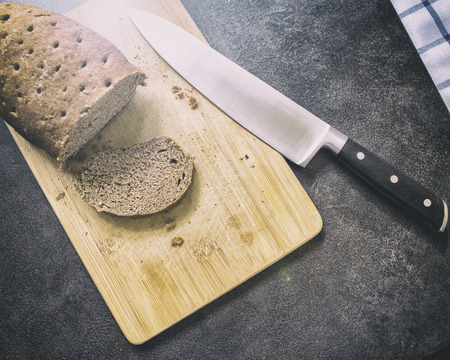 stale: hard stale bread and cut off a piece of it lie on a wooden cutting board, knife lying beside