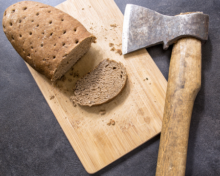hard stale bread and cut off a piece of it lie on a wooden cutting board, axe lying beside
