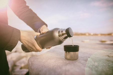 pours: Man pours hot tea from a thermos into a cup which stands on an ice floe on the river bank in the spring sunny day Stock Photo