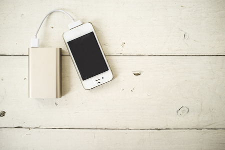 charged: Smartphone is charged from the portable charging device for shabby the wooden table painted in white color