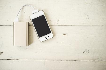 Smartphone wordt opgeladen via het draagbare oplaadapparaat voor de houten tafel in witte kleur Stockfoto