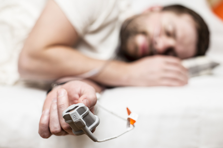 Sleep Apnea Diagnostic medical device Kit attached to the finger and the human nose, which lies in bed