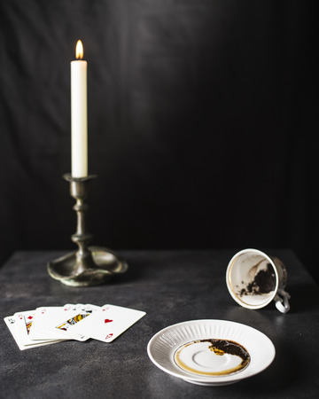 Fortune teller reading coffee grounds in the state are near a deck of cards and a candle in the old candlestick against the black background