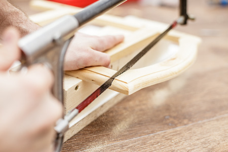 sawing: Man sawing a board with a hand saw wood, close-up Stock Photo