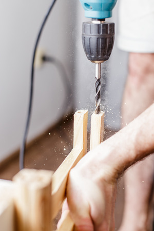 plywood: Man drilling a hole electric drill in a wooden plank at home in the living room Stock Photo