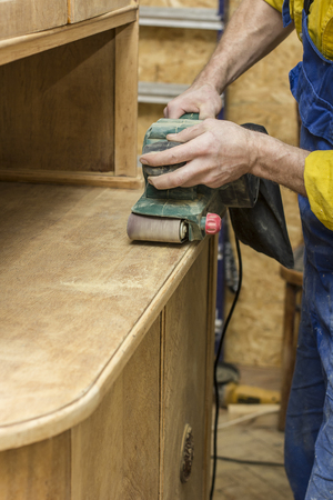 Carpenter restores vintage the wooden a sideboard by an electric of the grinding machine.