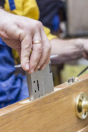pernos: El carpintero establece el en el viejo una cerradura de mortaja de madera de la puerta.