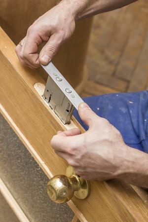 목수는 오래된 나무로되는 문에 장붓 구멍 자물쇠를 설치합니다.
