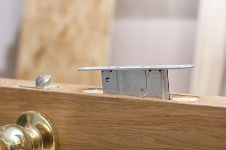 Mortise lock is inserted halfway into the old a wooden door.
