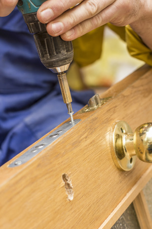 Carpenter attach using the screwdriver mortise lock in an old wooden door.