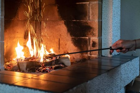 Female hand straightens burning firewood with an iron poker in an open fireplace and from the coal fly beautiful spark. Warmth and comfort in a cozy house, in winter.