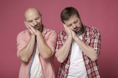 Two men jokingly folded palms, laid them under their heads and pretend to be sleeping.